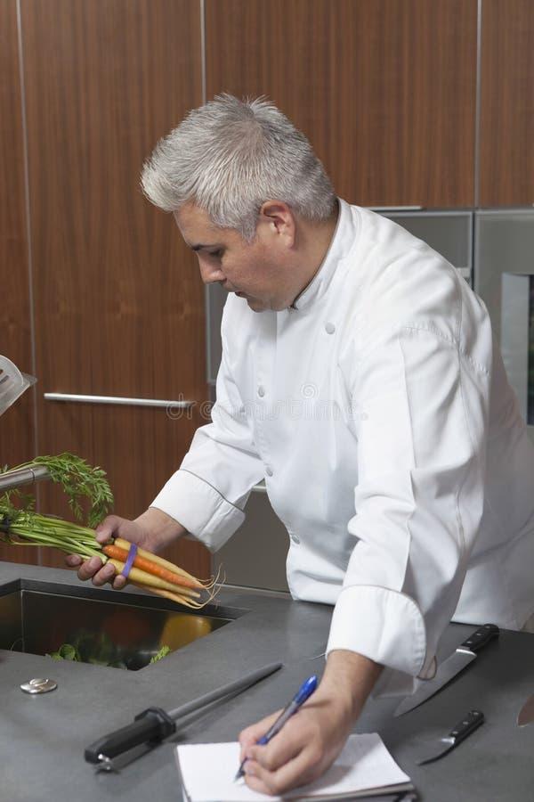 Chef-kok Holding Carrots And die in Notitieboekje schrijven royalty-vrije stock foto's