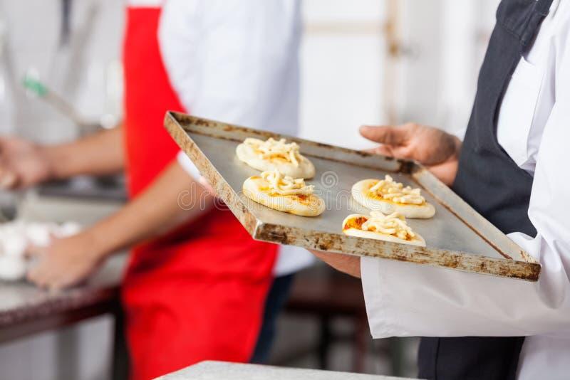 Chef-kok Holding Small Pizzas op Bakselblad binnen royalty-vrije stock afbeeldingen