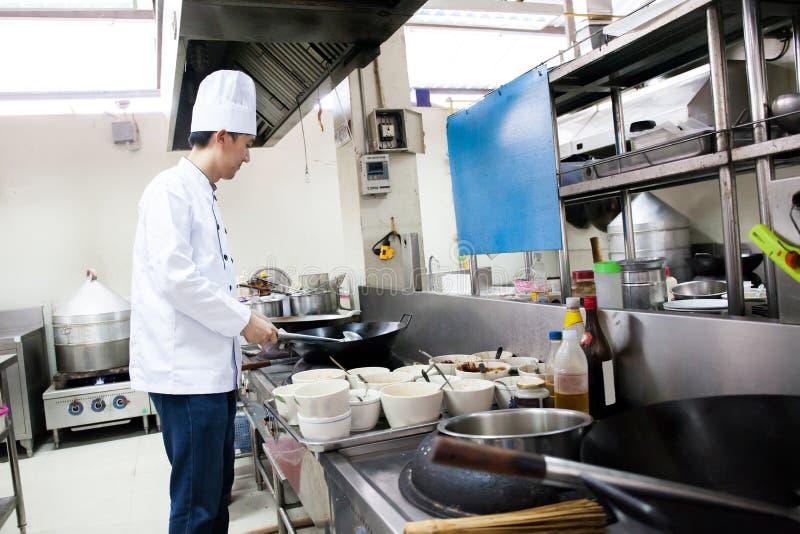 Chef-kok in hotel of restaurantkeuken bezig het koken stock foto