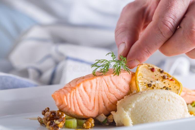 Chef-kok in hotel of restaurantkeuken het koken, slechts handen Voorbereid zalmlapje vlees met dilledecoratie royalty-vrije stock afbeelding