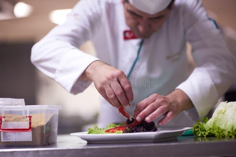 Chef-kok in hotelkeuken die en voedsel voorbereiden verfraaien royalty-vrije stock foto's