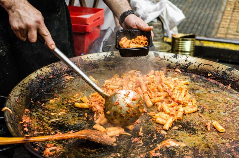 Chef-kok kokende deegwaren met tomatensaus en vlees bij een markt van het straatvoedsel stock foto's