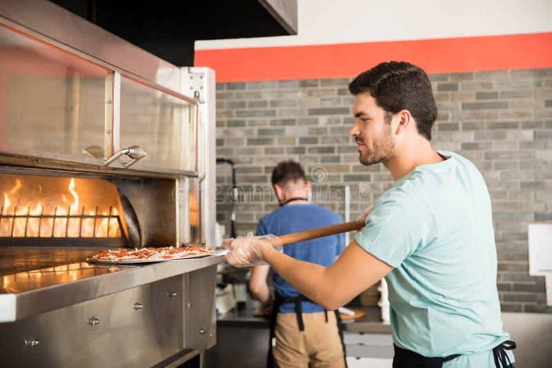 Chef-kok kokende pizza en het zetten van het in de te bakken oven stock foto