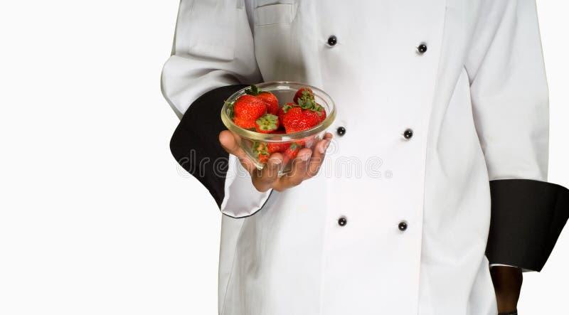Chef-kok met aardbeien stock fotografie