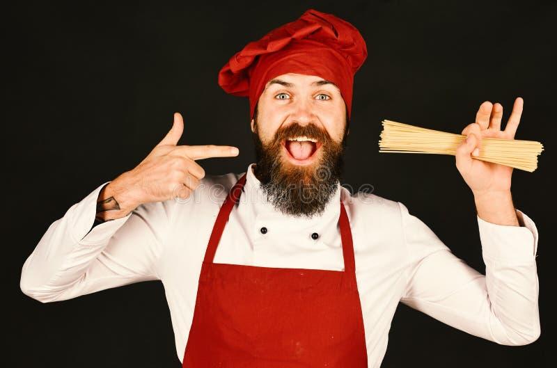 Chef-kok met bos van spaghetti Kok met vrolijk gezicht stock foto's