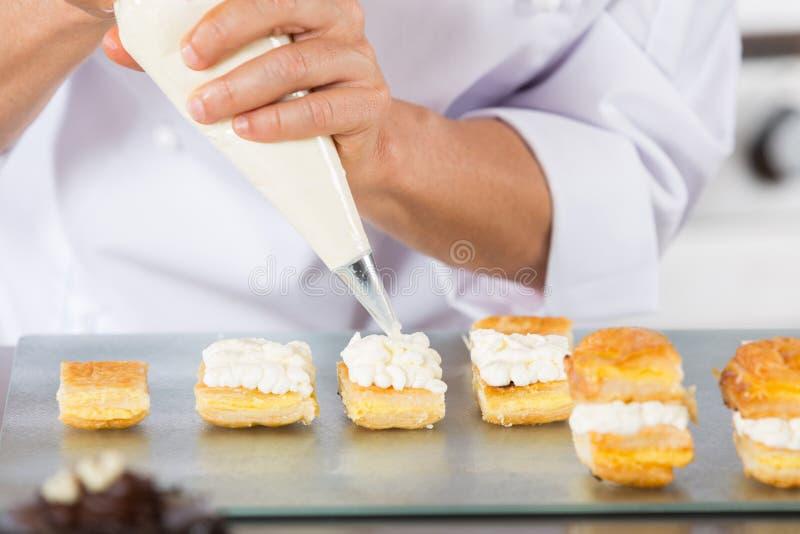 Chef-kok met een gebakjezak stock afbeelding