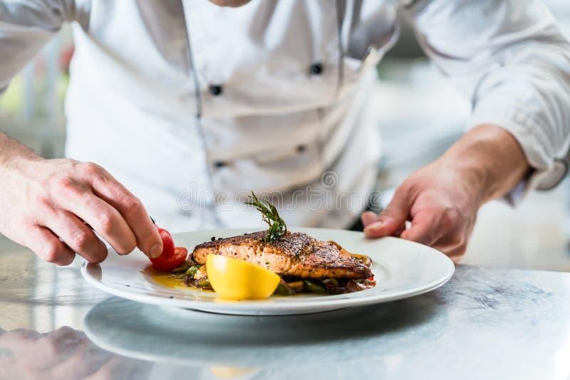 Chef-kok met ijver het eindigen schotel op plaat stock foto