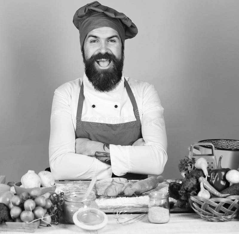 Chef-kok met kruiden, groenten en deeg op lijst Kok met vrolijk gezicht in de eenvormige dichtbijgelegen ingrediënten van Bourgon royalty-vrije stock afbeeldingen
