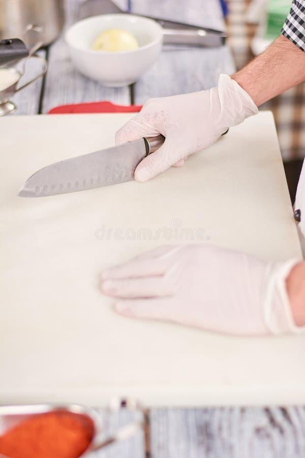 Chef-kok met mes en scherpe raad stock foto's