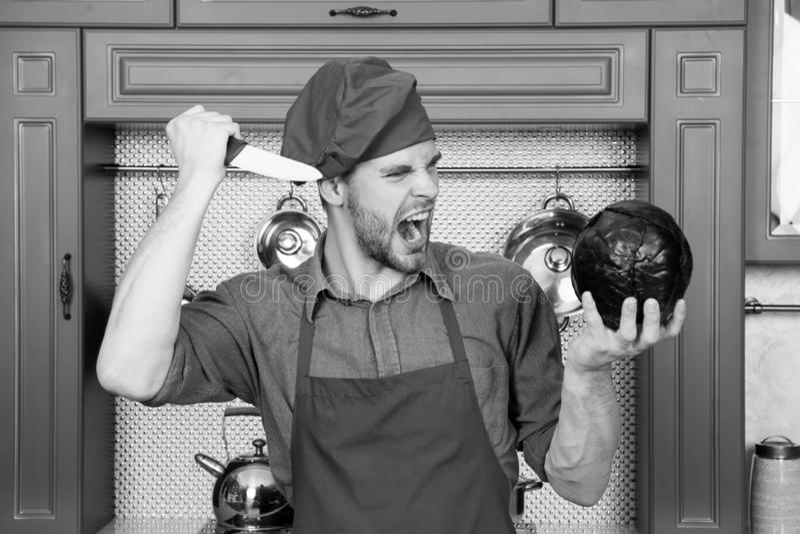 Chef-kok met messenschreeuw bij purpere kool Boze mens in rode hoed en schort in keuken Vegetarisch menu en gezonde voeding royalty-vrije stock foto