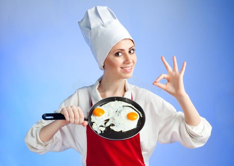 Chef-kok met pan en bradend ei royalty-vrije stock foto's