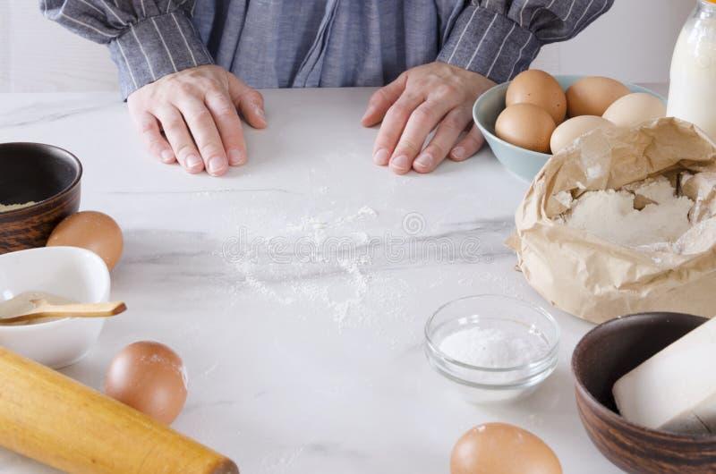 Chef-kok naast de keukenlijst, klaar om deeg te maken Vrouw die een schort dragen die klaar voor het maken van bakkerijproducten, stock fotografie