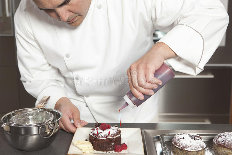 Chef-kok Puts Finishing Touches op Chocoladecake bij Keukenteller stock fotografie
