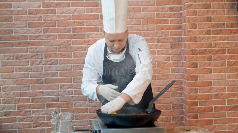 Chef-kok in restaurant die gebraden bol met zeevruchten in pan koken, die citroensap drukken royalty-vrije stock foto