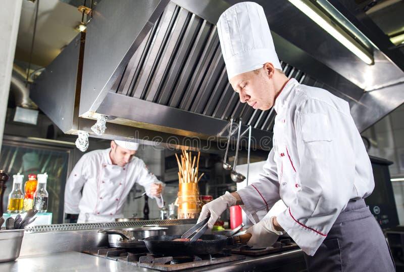 Chef-kok in restaurantkeuken bij fornuis met pan, het koken stock afbeelding