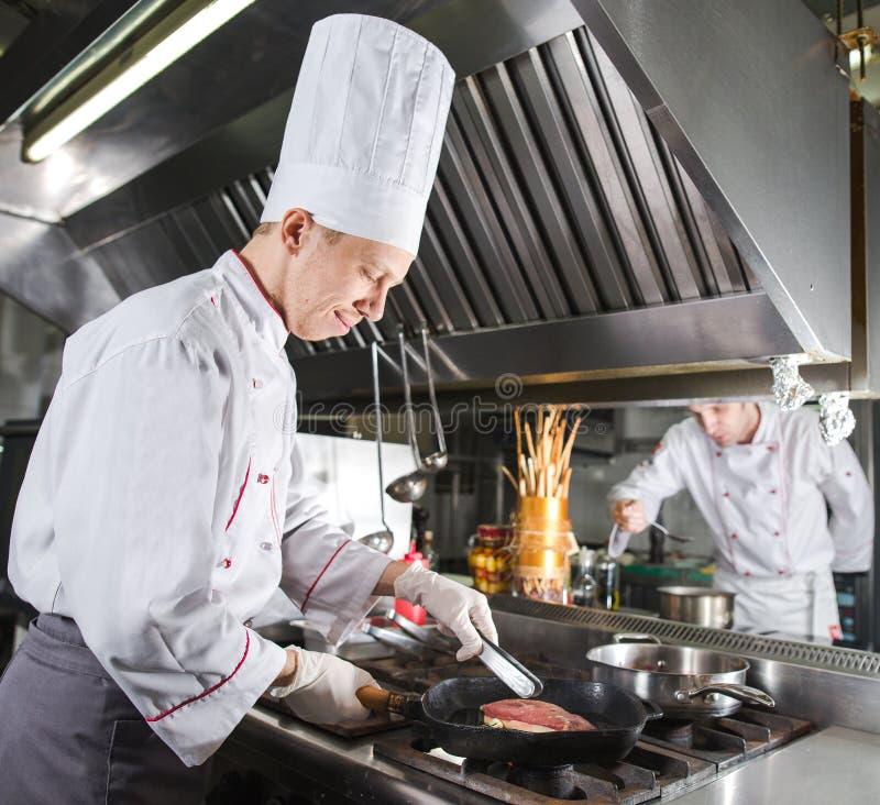 Chef-kok in restaurantkeuken bij fornuis met pan, het koken stock fotografie
