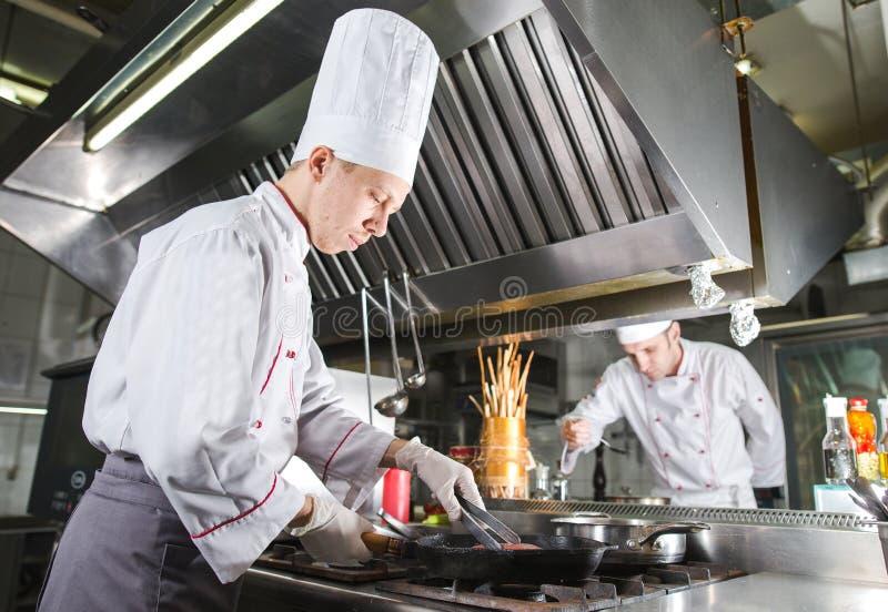 Chef-kok in restaurantkeuken bij fornuis met pan, het koken stock foto's