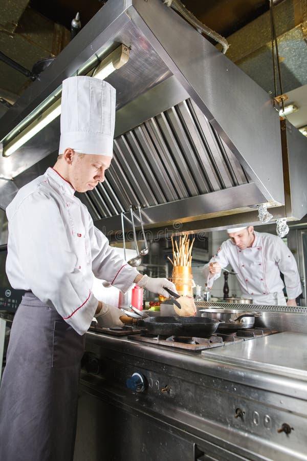 Chef-kok in restaurantkeuken bij fornuis met pan, het koken royalty-vrije stock foto