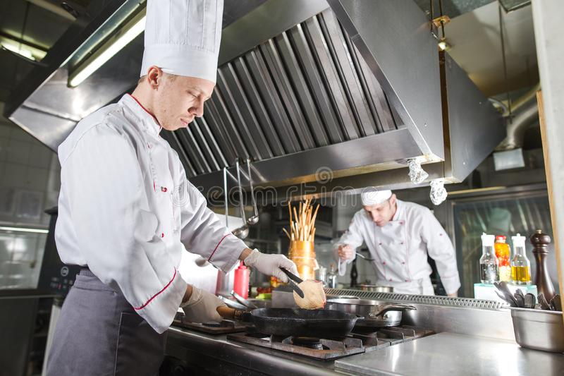 Chef-kok in restaurantkeuken bij fornuis met pan, het koken royalty-vrije stock fotografie