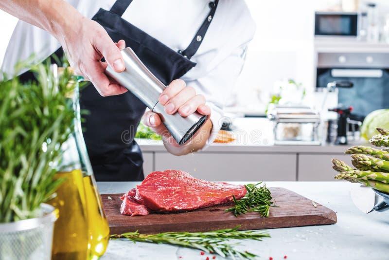 Chef-kok in restaurantkeuken het koken, is hij scherp vlees of lapje vlees stock afbeeldingen