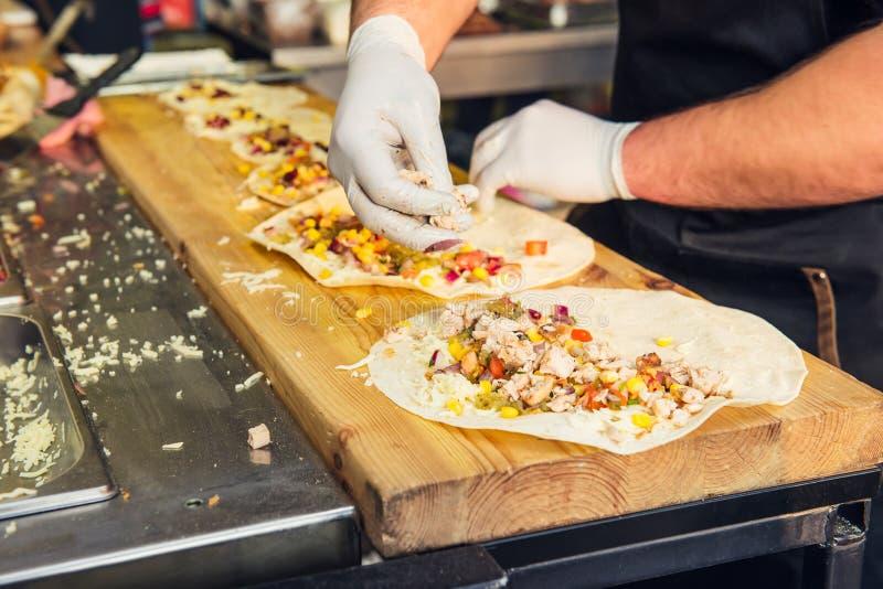 Chef-kok` s handen die Mexicaanse taco's voorbereiden bij een markt van het straatvoedsel, festival, gebeurtenis Proces het koken royalty-vrije stock fotografie