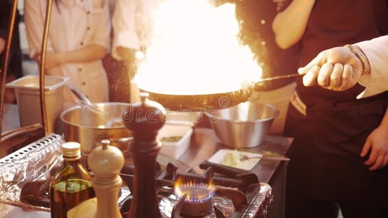 Chef-kok ` s Masterclass Chef-kok Cooking With Fire in Pan nProfessionalchef-kok In een Commerciële Keuken die Flambe-Stijl koken stock videobeelden