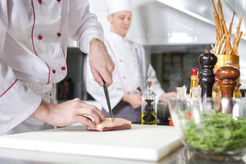 Chef-kok scherp vlees op hakbord, het professionele mes van de kokholding en scherp vlees in restaurant stock fotografie