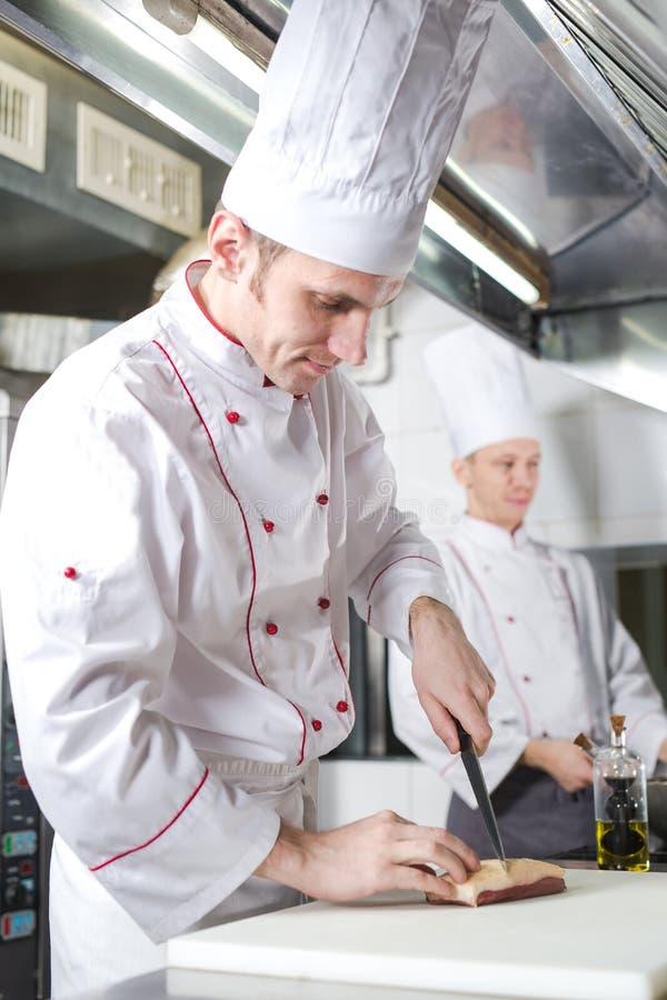 Chef-kok scherp vlees op hakbord, het professionele mes van de kokholding en scherp vlees in restaurant stock foto