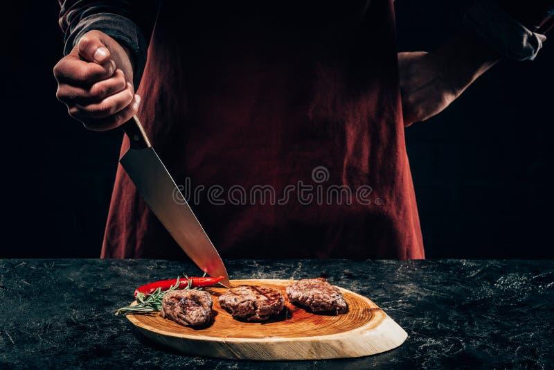 Chef-kok in schort met vleesvork en mes die gastronomische geroosterde lapjes vlees met rozemarijn en Spaanse peperpeper op houte royalty-vrije stock afbeeldingen