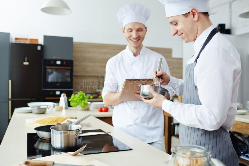Chef-kok tevreden met het studentenwerk stock fotografie