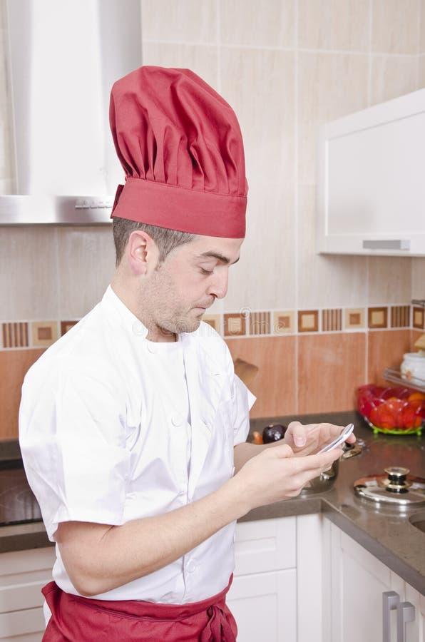 Chef-kok wat betreft smartphone in de keuken royalty-vrije stock fotografie