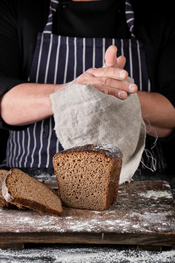 chef-kok in zwart eenvormig gesneden gebakken roggebrood op een bruine houten die raad met witte bloem wordt bestrooid royalty-vrije stock foto