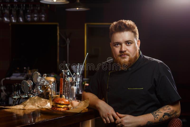 Chef-kok in zwarte eenvormig voorstellend een dienblad met hamburger royalty-vrije stock afbeelding
