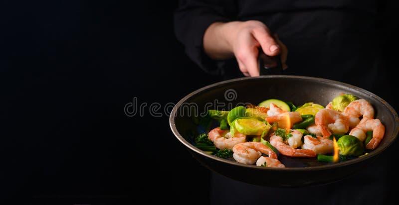 Chef kokar räkor med grönsaker, i en form med brand Frysning och kokning Oriental cuisine Kultur- och restaurangbranschen. royaltyfria bilder