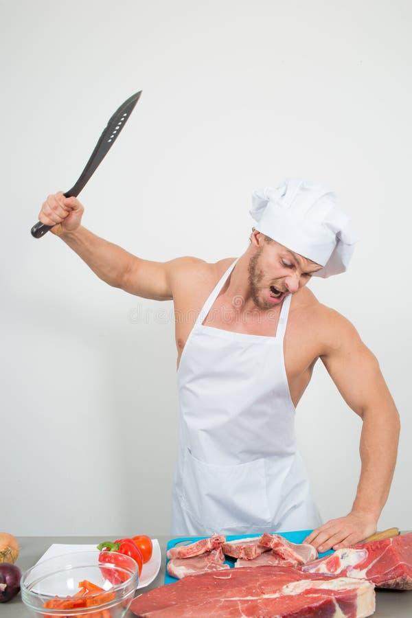 Chef-kokbodybuilder die grote brokken van ruw vlees voorbereiden natuurlijke proteïnen royalty-vrije stock foto