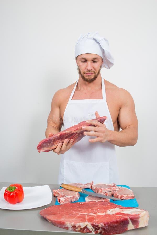 Chef-kokbodybuilder die grote brokken van ruw vlees voorbereiden natuurlijke proteïnen royalty-vrije stock afbeeldingen