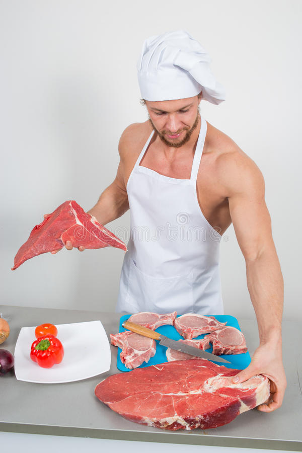 Chef-kokbodybuilder die grote brokken van ruw vlees voorbereiden natuurlijke proteïnen stock afbeeldingen
