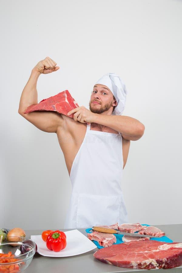 Chef-kokbodybuilder die grote brokken van ruw vlees voorbereiden natuurlijke proteïnen royalty-vrije stock fotografie