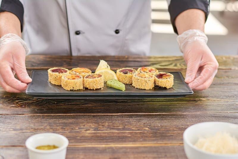 Chef-kokhanden die plaat met sushibroodjes houden royalty-vrije stock foto's