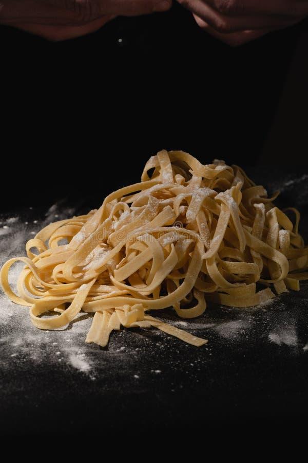 Chef-kokhanden die spaghetti, deegwaren, noedels met verse deegwaren op zwarte lijst maken met stock foto