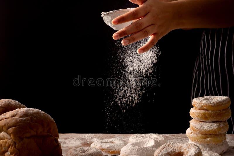 Chef-kokhanden die voorbereidend brooddeeg en doughnut met suikerglazuursuiker bestrooien op houten die lijst op zwarte achtergro royalty-vrije stock afbeeldingen