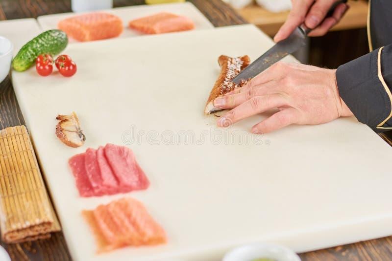 Chef-kokhanden met mes die gerookte paling snijden stock foto's