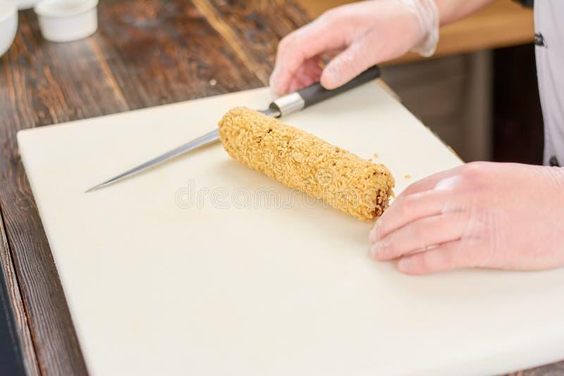 Chef-kokhanden met mes en lang sushibroodje stock fotografie
