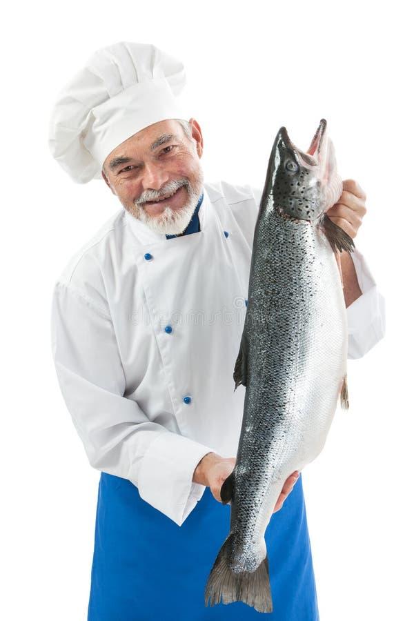 Chef-kokkok die een grote Atlantische zalmvis houden stock fotografie