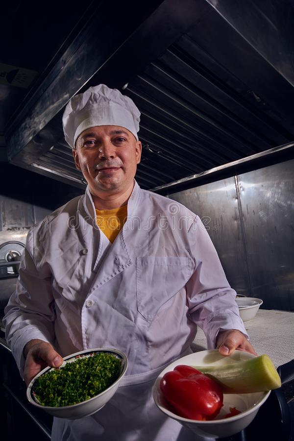 Chef-kokkok in een witte schort en kokshoed op een keuken die zijn mooi werk doen royalty-vrije stock afbeeldingen