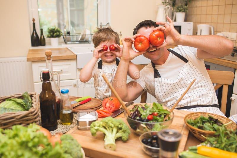 Chef-kokmens het koken op de keuken met weinig zoon royalty-vrije stock afbeelding
