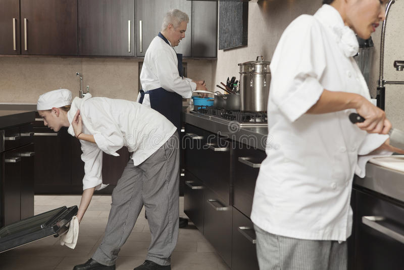 Chef-koks die in Commerciële Keuken samenwerken stock foto