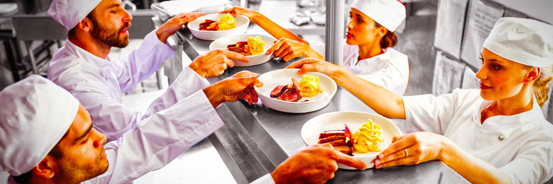 Chef-koks die klaar voedsel overgaan tot kelner bij ordepost stock fotografie