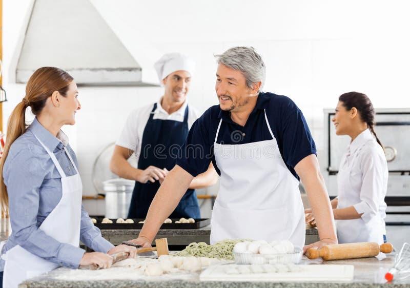 Chef-koks die terwijl het Voorbereiden van Deegwaren bij Keuken spreken royalty-vrije stock afbeeldingen