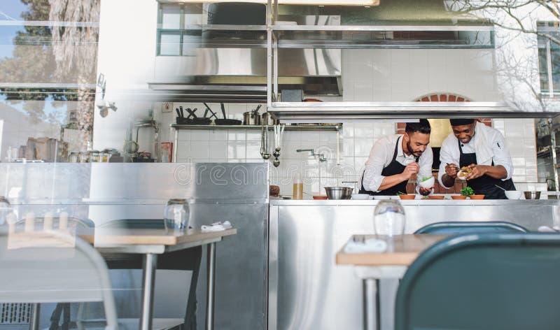 Chef-koks die voedsel koken samen bij restaurantkeuken stock afbeeldingen